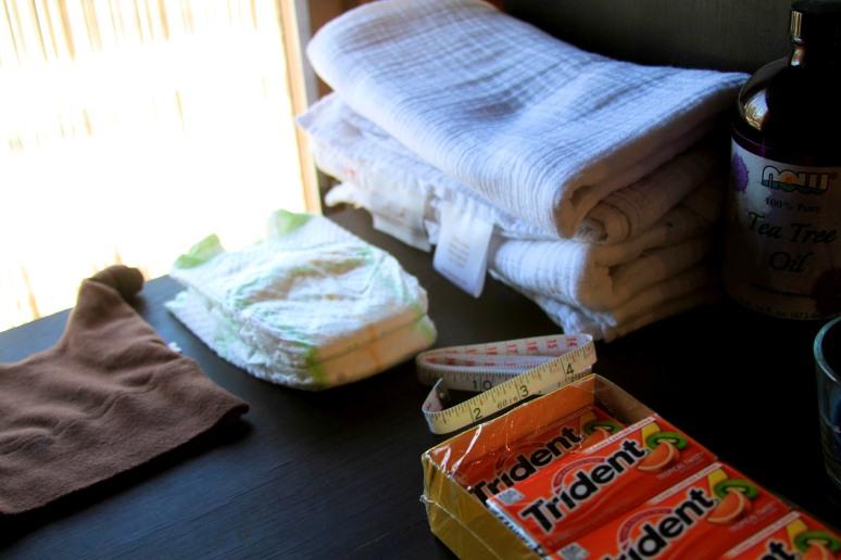Newborn cap, diapers, blankets, measuring tape, tea tree oil and gum